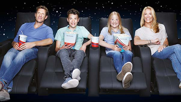 Family sitting on cinema chairs